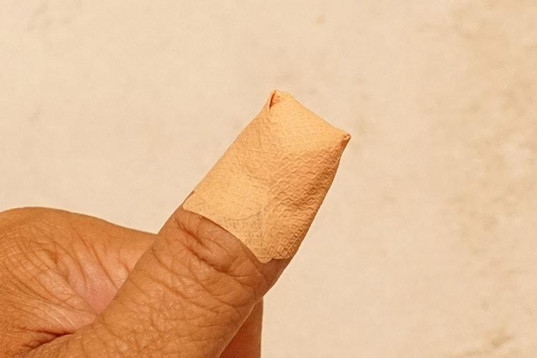 ロコベースリペアクリームを指のひび割れに塗り、上から絆創膏を巻く
